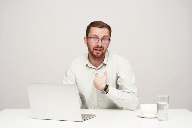Озадаченный молодой красивый небритый светловолосый мужчина смущенно смотрит в камеру и гримасничает, сидя за столом с ноутбуком на белом фоне