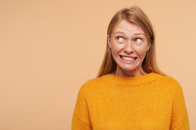 Perplesso giovane bella donna dai capelli lunghi rossa con trucco naturale che fa smorfie confusamente il suo viso mentre guarda da parte, isolata contro il beige