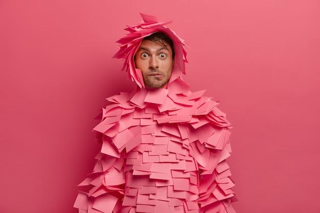 Озадаченный молодой человек кусает губы и выглядит удивительно, реагирует на удивительные новости, мастерит забавный костюм из наклеек, позирует в помещении на фоне ярко-розовой стены. концепция выражения лица человека