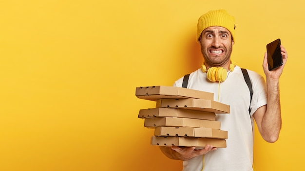 Puzzled young man carries cardboard boxes of pizza, holds mobile phone, being busy with delivering, has many orders, deadline for transporting, wears yellow hat and white t shirt, stands indoor