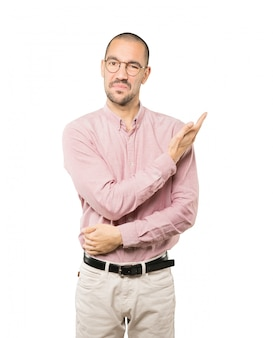 Puzzled young man doing a gesture of not understand