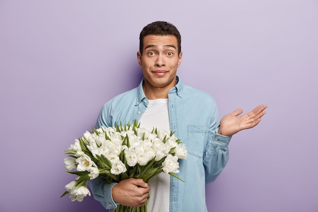 Puzzled young man holds big bouquet of flowers, raises hand with indignantion, comes on date