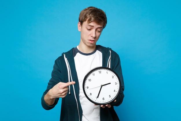 Озадаченный молодой человек в повседневной одежде держит, указывая указательным пальцем на круглые часы, изолированные на синей стене. время уходит. концепция образа жизни искренние эмоции людей.