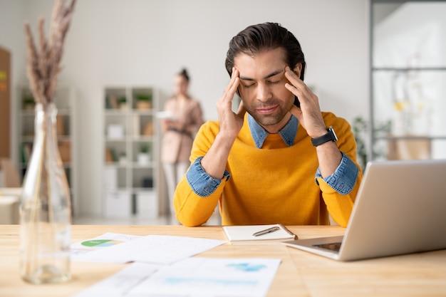 Озадаченный молодой человек в желтом свитере сидит за столом с блокнотом и держит голову руками, страдая от головной боли на работе