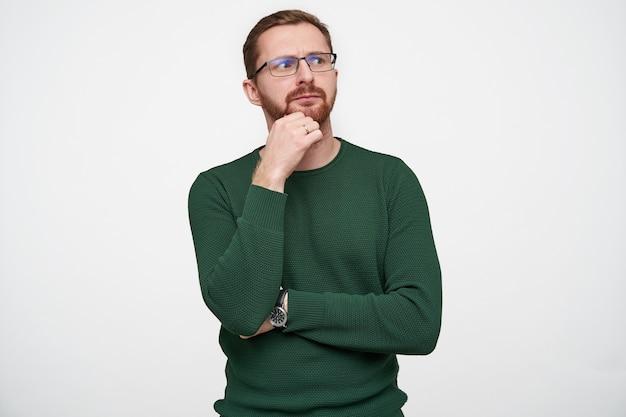 Perplesso giovane bella mora maschio dai capelli corti in occhiali tenendo la mano sotto il mento e le sopracciglia accigliate mentre guarda da parte, in piedi