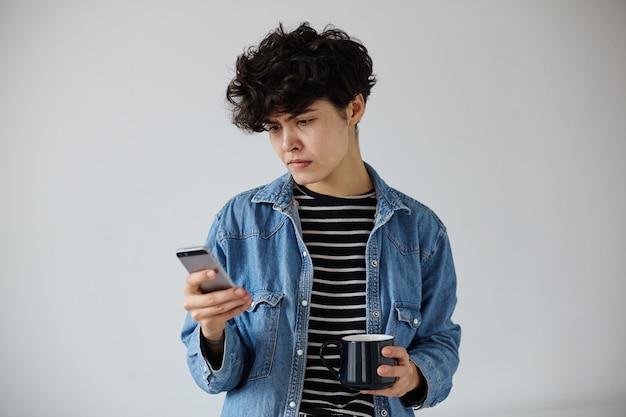 Озадаченная молодая симпатичная кудрявая брюнетка с короткой модной стрижкой держит смартфон в руке и смущенно смотрит на экран, позирует на белом фоне с темной керамической чашкой