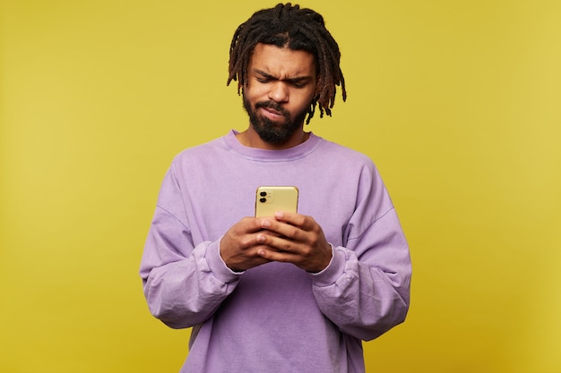 Puzzled young pretty dark skinned bearded man frowning his face while looking confusedly on screen of his mobile phone, isolated over yellow background