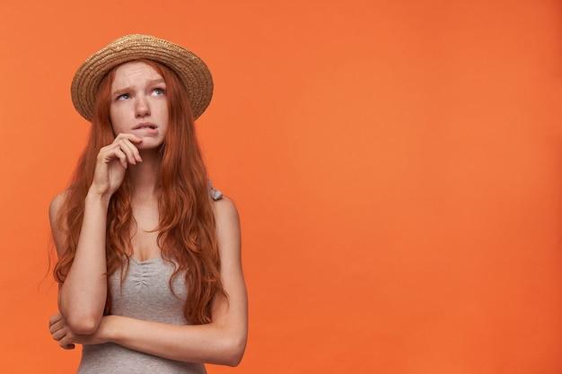 Giovane donna graziosa perplessa con capelli ondulati foxy che si appoggia il viso sulla mano sollevata e guarda da parte dubbiosa, posa su sfondo arancione in abiti casual