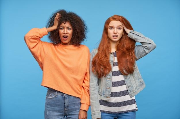 彼女の顔を眉をひそめ、混乱して見ている、困惑した若いきれいな女性は、カジュアルな服装で青い壁の上にポーズをとっている間、彼女の頭に手を上げたままにします