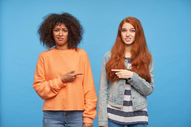 Giovani donne graziose perplesse che indicano l'un l'altro con le dita indice e facce confuse mentre guardano, isolate sopra il muro blu
