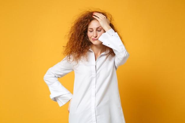 Озадаченная рыжая девушка в повседневной белой рубашке позирует изолированно на желто-оранжевой стене