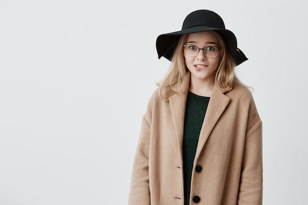 困惑した若い女性が唇を曲げ、何かを考え、重要なことを思い出そうとしています。コートと黒い帽子の疑わしい女性が混乱している困難な状況で解決策を見つける