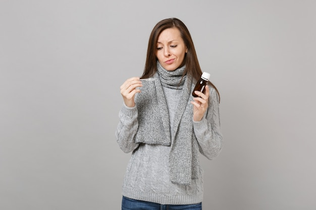 Puzzled young woman in gray sweater, scarf holding pour liquid medicine into spoon isolated on grey background. healthy lifestyle, ill sick disease treatment, cold season concept. mock up copy space.
