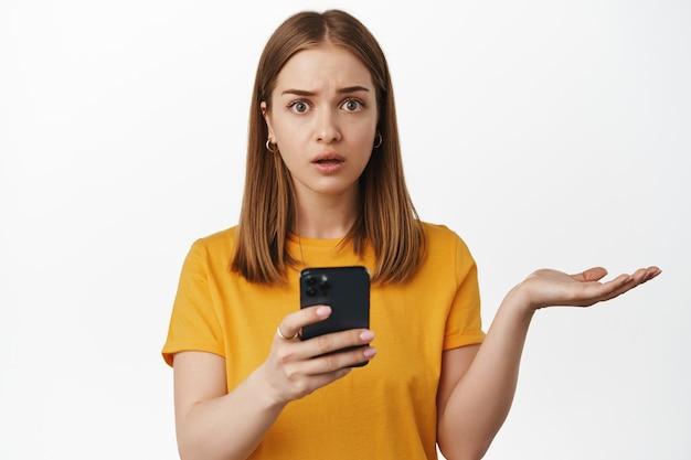 スマートフォンアプリを使用した後、白い壁の上に立って、電話を持って、理解できない、肩をすくめる、無知に見える困惑した若い女性