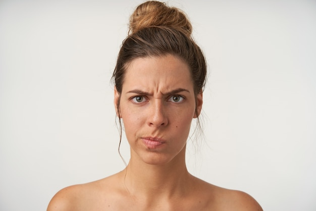 真面目な顔と眉をひそめている白の上に立っている高いお団子髪型の困惑した若い女性