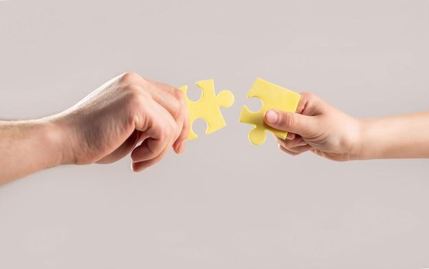 パズル。子供の手と母の手折りパズル、クローズアップ