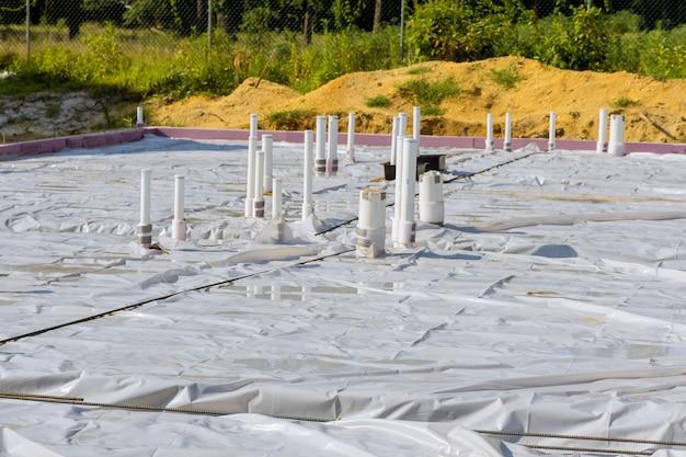 건설 현장에서 콘크리트를 붓기 위한 기초 슬래브 준비의 새 집에 있는 pvc 배수관.
