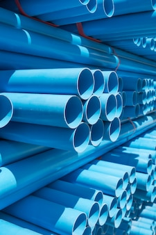 Pvc pipes stacked in warehouse.