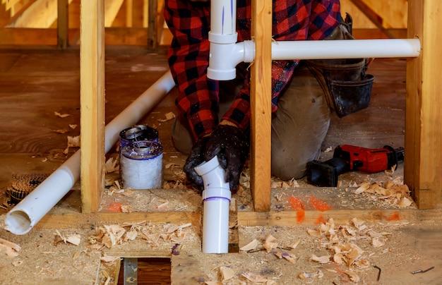 Pvc排水管、クローズアップに接着剤を置く配管工