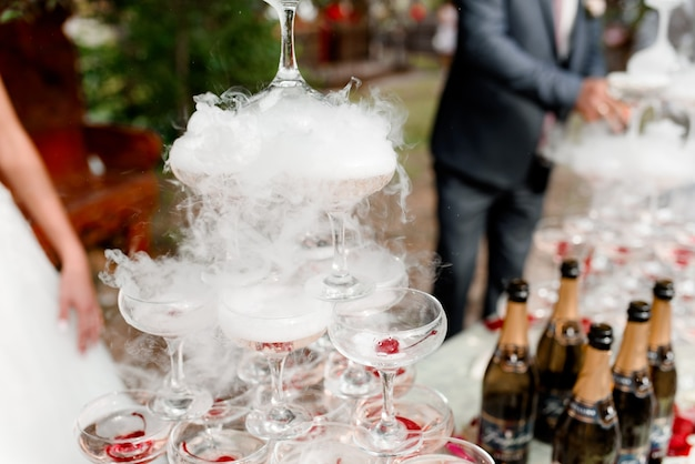 Pyramid of cocktails with champagne and cherries in liquid nitrogen smoke
