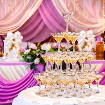 Pyramid of glasses with champagne in purple wedding interior.