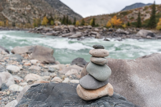 Pyramid and a hill of stones on the background of a mountain river