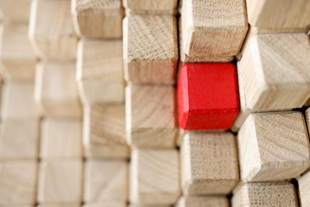 베이지 색 나무 큐브의 피라미드 중 하나는 빨간색입니다. 수익성있는 상업 제공 개념