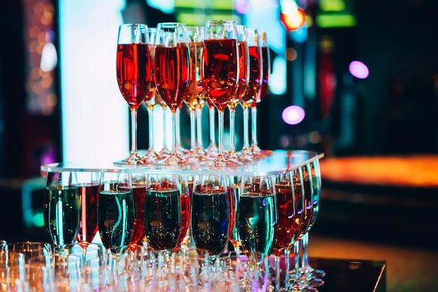 Пирамида из бокалов для шампанского. много бокалов шампанского на баре. пузыри шампанского в бокале. цветное шампанское.