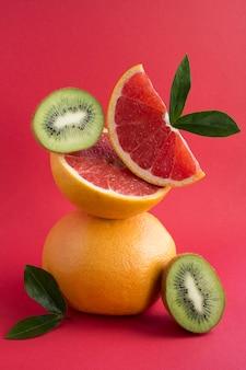 赤の背景にバランスのとれたグレープフルーツとキウイのピラミッド。
