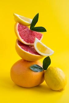黄色の壁にバランスのとれたグレープフルーツとレモンのピラミッド。クローズアップ。場所は垂直です。