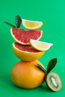 緑の背景にバランスのとれたグレープフルーツ、キウイ、レモンのピラミッド。