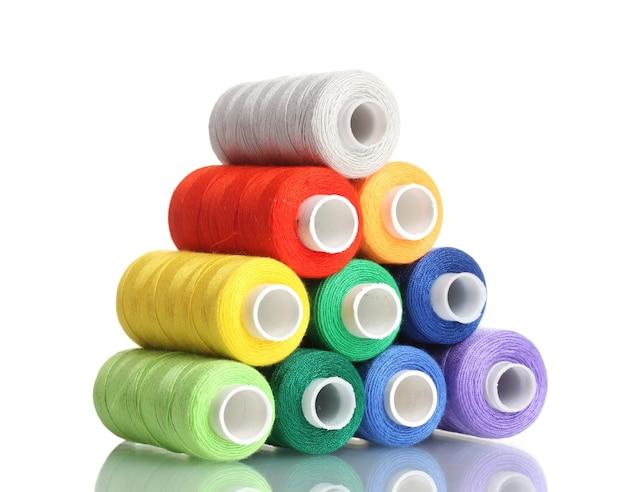 白で隔離される糸の多くの色のボビンのピラミッド