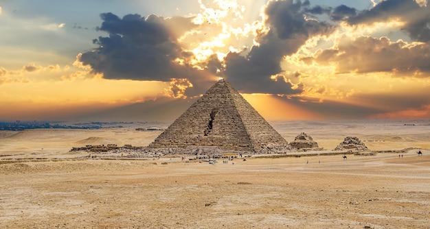 Пирамида менкаура. древняя пирамида против неба. пирамида менкаура и пирамиды королев, каир. пирамида менкаура - самая маленькая из трех главных пирамид гизы.