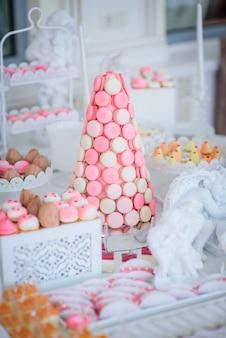 Пирамида розовых и белых макаронов стоит на конфетах