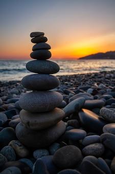 Пирамида из морских камней на берегу моря на закате. понятие гармонии и баланса.