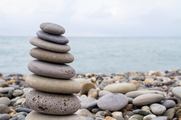 Пирамида из морских камней на берегу моря на галечном пляже. понятие гармонии и баланса.