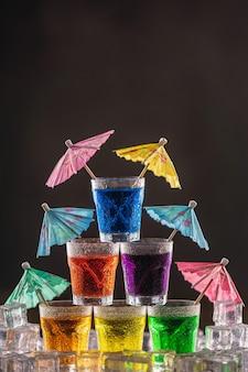 Пирамида из шотов с разноцветным алкоголем, украшенная зонтиками для коктейлей