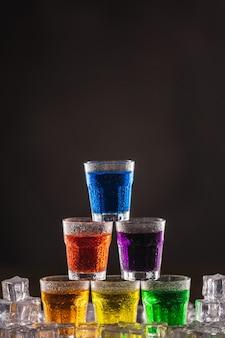 Пирамида выстрелов с разноцветным алкоголем на льду