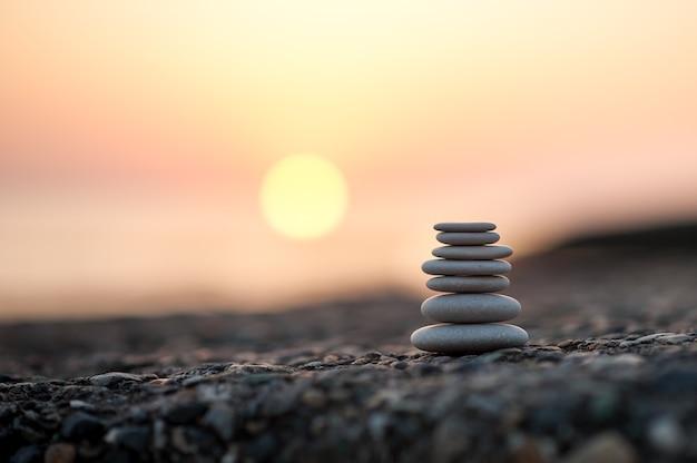 Пирамида из камней на берегу моря на закате. сбалансированные дзен-камни.