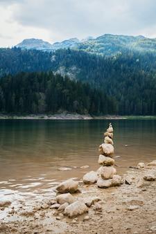Пирамида из камней сложена на берегу черного озера в черногории.