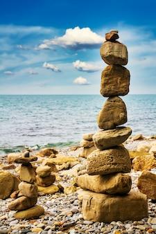 Пирамида из камней на берегу моря на галечном пляже