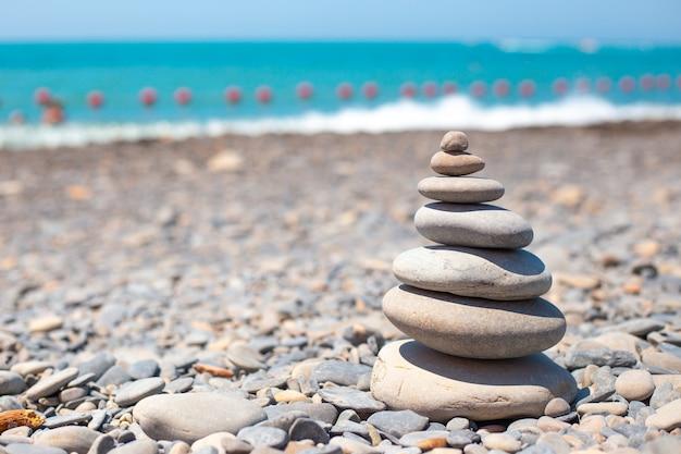 Пирамида из камней на берегу моря путешествия и туризм копируют пространство слева