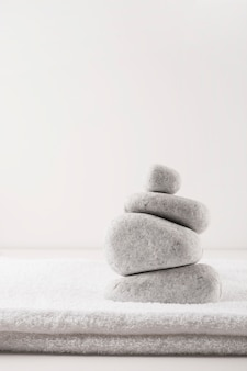 Pyramid of the stones over clean folded towel isolated on white background