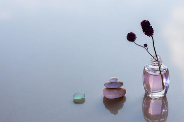 Пирамида из трех камней и бутылок с розовым маслом и прилепленной веткой
