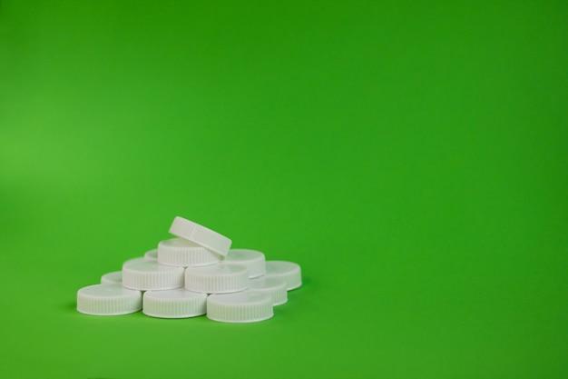 緑の背景に白いペットボトルのキャップのピラミッド。環境汚染。プラスチックのコンセプトをリサイクルします。