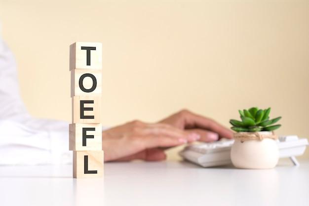 フォアグラウンド、バックグラウンドにtoeflという単語が表示された木製の立方体のピラミッド-ビジネスウーマンは、明るいオフィスの空きスペースでキーボードを操作します。セレクティブフォーカス
