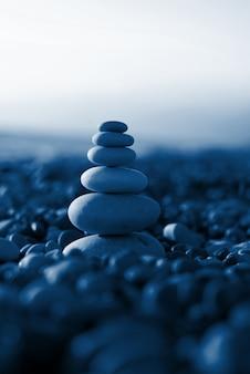 Pyramid of pebbles on the beach sea. illuminated by the sun