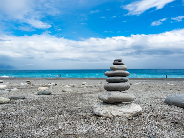 Pyramid of sea pebbles on a sunny sand beach in hualien,taiwan.