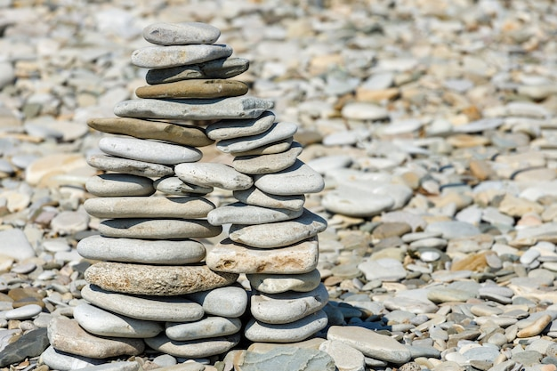 Pyramid of sea stones on the beach in summer. high quality photo