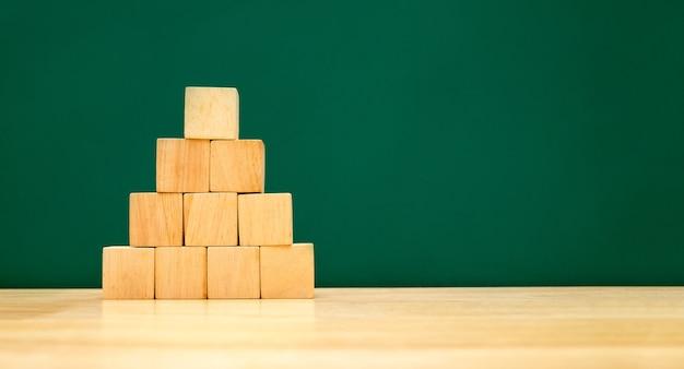 Формирование пирамиды из деревянного куба на деревянном столе с зеленой доской на фоне